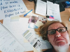 Sarah drowns in a sea of papers, notes, flyers...